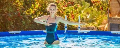 Mujer activa en la piscina que hace aeróbicos de agua Imagen de archivo