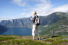 Mujer activa en la tapa de montañas sobre el lago Foto de archivo libre de regalías