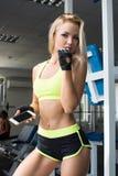 Mujer activa en ropa de deportes usando el teléfono elegante en el gimnasio Conviértase mejor Fuerza de la voluntad Carrocería he Imágenes de archivo libres de regalías