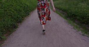 Mujer activa en vestido colorido que camina en manera de la grava Tiro del PDA metrajes