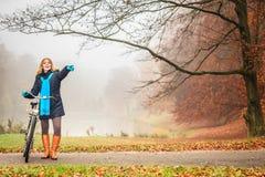 Mujer activa feliz con la bici en parque del otoño Imagen de archivo libre de regalías