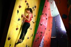 Mujer activa joven Bouldering en roca artificial colorida en gimnasio que sube Deporte extremo y concepto que sube interior fotos de archivo