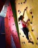 Mujer activa joven Bouldering en roca artificial colorida en gimnasio que sube Deporte extremo y concepto que sube interior fotografía de archivo