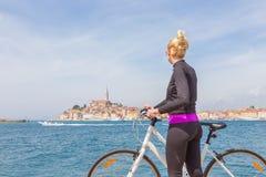 Mujer activa joven que completa un ciclo alrededor de Rovinj, Istria, Croacia Fotografía de archivo