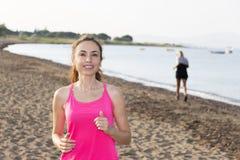 Mujer activa que activa por una playa Fotos de archivo