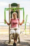 Mujer activa que ejercita en la prensa del pecho al aire libre imagen de archivo