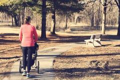 Mujer activa que empuja un cochecito a través de un parque fotos de archivo