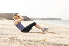 Mujer activa que hace Sentar-UPS por la playa imagen de archivo