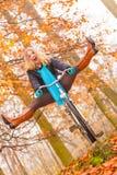 Mujer activa que tiene bici del montar a caballo de la diversión en parque del otoño Imagenes de archivo