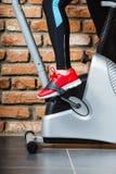 Mujer activa que usa la bicicleta estática en el gimnasio Imagenes de archivo