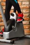 Mujer activa que usa la bicicleta estática en el gimnasio Imagen de archivo libre de regalías