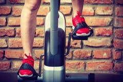 Mujer activa que usa la bicicleta estática en el gimnasio Fotos de archivo