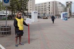 Mujer-activista con la inscripción en la ropa: 1500 familias engañadas - soportes contra la perspectiva de la ciudad imagenes de archivo