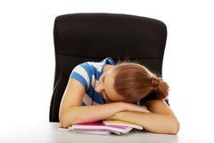 Mujer adolescente agotada que duerme en el escritorio Foto de archivo libre de regalías