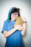 Mujer adolescente bastante joven alegre con el paquete del regalo del oro Imagenes de archivo