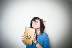 Mujer adolescente bastante joven alegre con el paquete del regalo del oro Foto de archivo