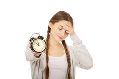 Mujer adolescente cansada con el despertador Fotos de archivo libres de regalías