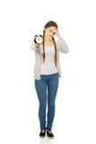 Mujer adolescente cansada con el despertador Fotos de archivo