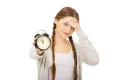 Mujer adolescente cansada con el despertador Imagen de archivo