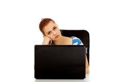Mujer adolescente cansada con el ordenador portátil que se sienta detrás del escritorio Fotos de archivo libres de regalías