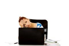 Mujer adolescente cansada con el ordenador portátil que se sienta detrás del escritorio Imagen de archivo libre de regalías