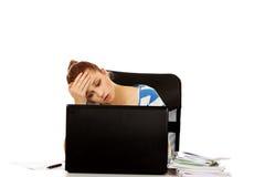 Mujer adolescente cansada con el ordenador portátil que se sienta detrás del escritorio Imagenes de archivo