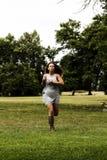 Mujer adolescente caucásica que corre en el parque Gray Dress Imágenes de archivo libres de regalías