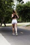 Mujer adolescente caucásica que corre en la trayectoria de la bici Imagenes de archivo
