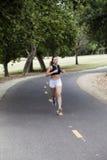 Mujer adolescente caucásica que corre en la trayectoria de la bici en parque Foto de archivo