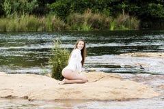 Mujer adolescente caucásica que se sienta en la suciedad en leotardo del blanco del río Imagenes de archivo