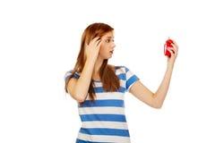 Mujer adolescente chocada con el despertador Fotos de archivo