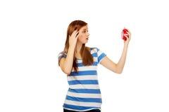 Mujer adolescente chocada con el despertador Imagen de archivo libre de regalías
