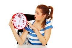 Mujer adolescente chocada jóvenes que mira el reloj Imagenes de archivo
