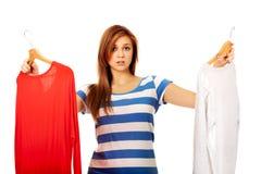 Mujer adolescente con dos camisas que piensa qué vestirse Fotografía de archivo libre de regalías
