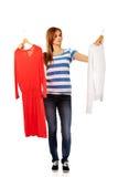 Mujer adolescente con dos camisas que piensa qué vestirse Fotos de archivo