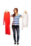 Mujer adolescente con dos camisas que piensa qué vestirse Fotografía de archivo