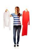 Mujer adolescente con dos camisas que piensa qué vestirse Imagen de archivo