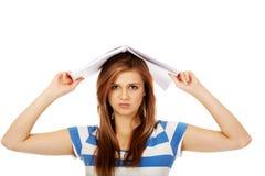 Mujer adolescente con el cuaderno en la cabeza Imágenes de archivo libres de regalías