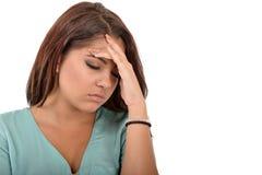 Mujer adolescente con el dolor de cabeza que lleva a cabo su mano a la cabeza Foto de archivo