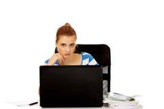 Mujer adolescente con el ordenador portátil que se sienta detrás del escritorio Fotografía de archivo libre de regalías