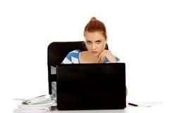 Mujer adolescente con el ordenador portátil que se sienta detrás del escritorio Imágenes de archivo libres de regalías