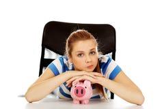 Mujer adolescente con el piggybank en la tabla Imágenes de archivo libres de regalías