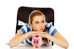 Mujer adolescente con el piggybank en la tabla Fotografía de archivo