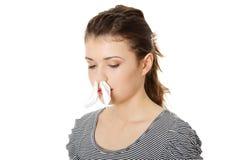 Mujer adolescente con el tejido en su nariz Fotos de archivo