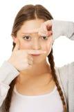 Mujer adolescente con gesto del marco Imagen de archivo libre de regalías