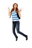Mujer adolescente con la mochila que salta y que gesticula paz Imagen de archivo libre de regalías