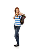 Mujer adolescente con la mochila que señala en la cámara Foto de archivo libre de regalías