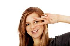 Mujer adolescente con la muestra de la victoria en ojo Fotografía de archivo