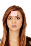 Mujer adolescente con las notas pegajosas sobre la frente Imagenes de archivo