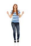 Mujer adolescente con los brazos extendidos que miran para arriba Foto de archivo libre de regalías